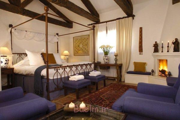 schlafzimmer gestalten metallbett betthimmel rankenmuster rustikale zimmereinrichtung kamin kerzen