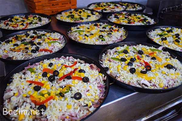 تو آشپرخونه ، پیتزاها در حال آماده شدن برای رفتن تو فر هستن